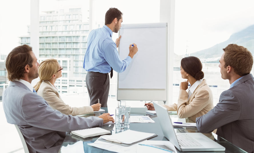 boss demonstrating to employees on whiteboard